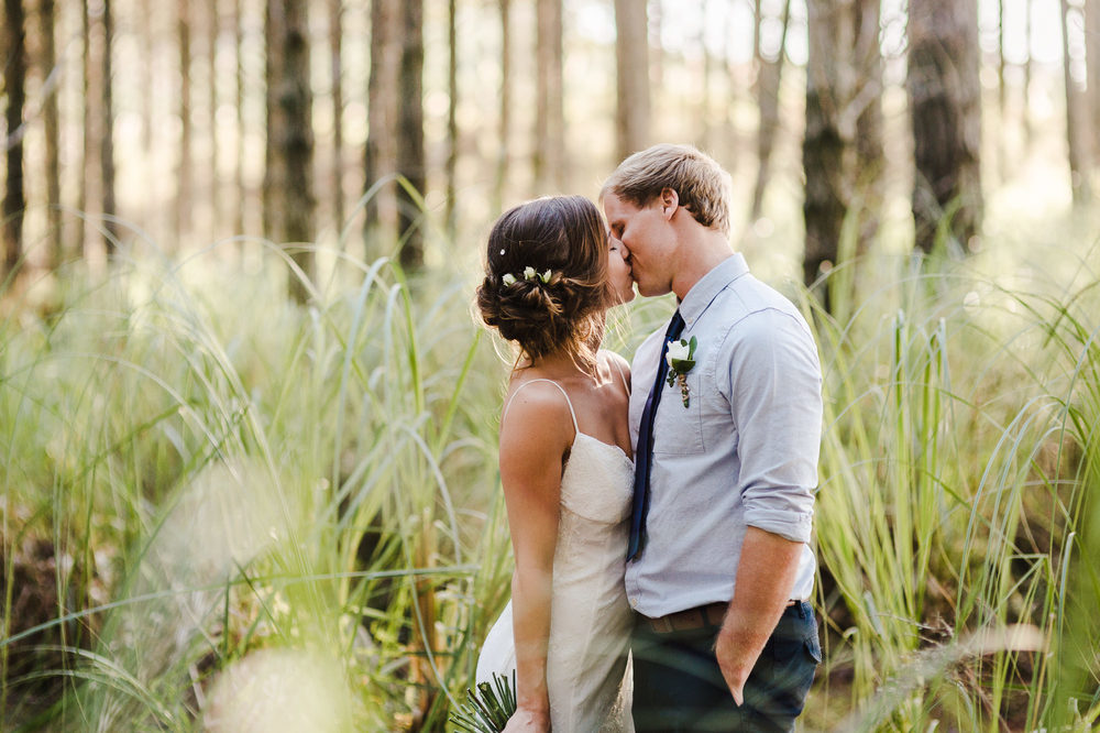 kissing wedding couple in woods.jpg