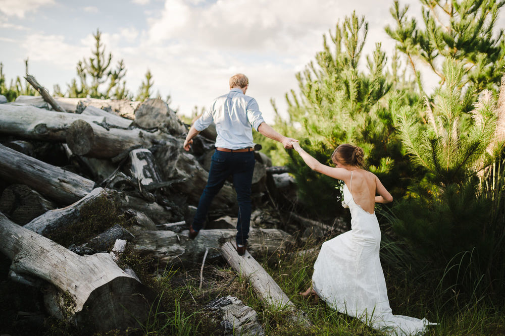 adventurous bride and groom climbing pile of logs.jpg