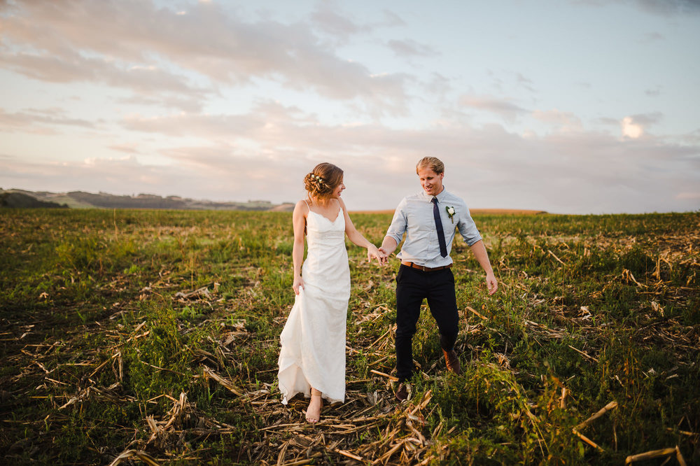 wedding couple walking through corn field at sunset.jpg