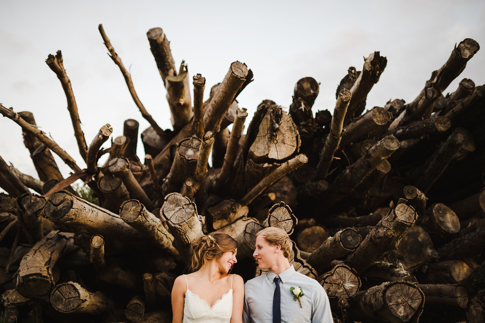 bride and groom with pile of logs.jpg