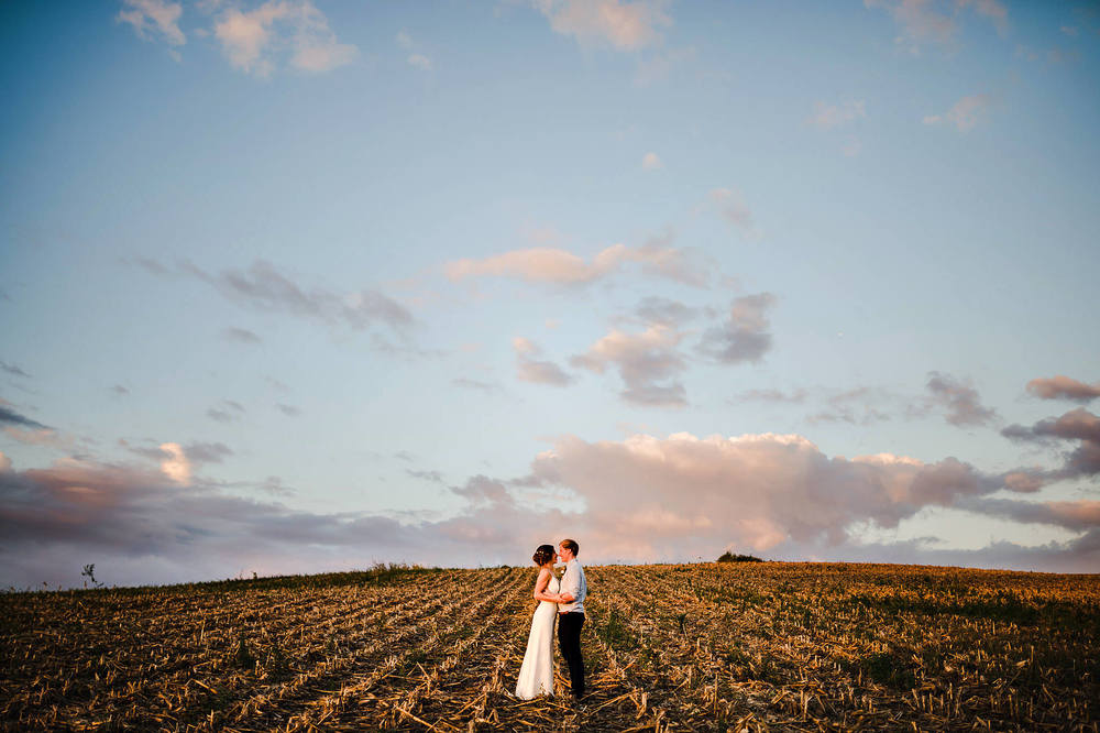 bride and groom in field at sunset auckland wedding photography.jpg