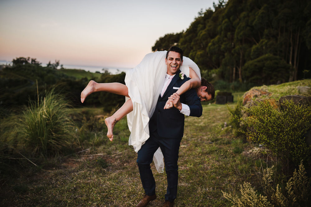 16 Funny moment groom carrying bride over his shoulders fireman hold barefoot bride relaxed New Zealand weding.JPG