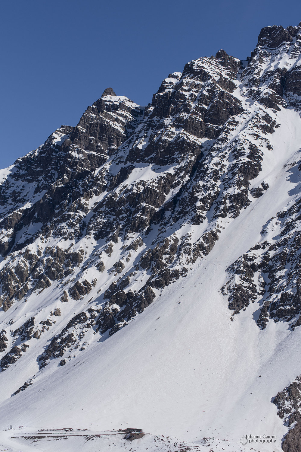 "Roca Jack is served by a slingshot and to give you a sense of scale the slingshot loading area is just above the Roca Jack written at the start of this caption. The lift serves about halfway up to the top ridgeline, the rest must be hiked for the Super C, with ""no fall zone"" traverses going left across the cliffs for great runs like Cara Cara, S Chute, Le Stadio, and more."