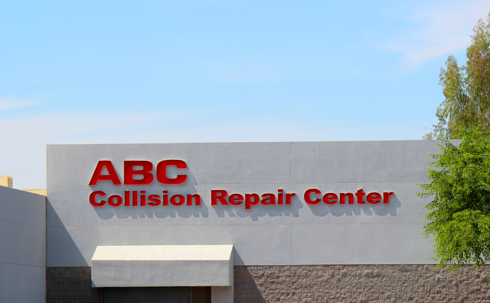 The set of illuminated channel letters brands the dealership's collision repair center.