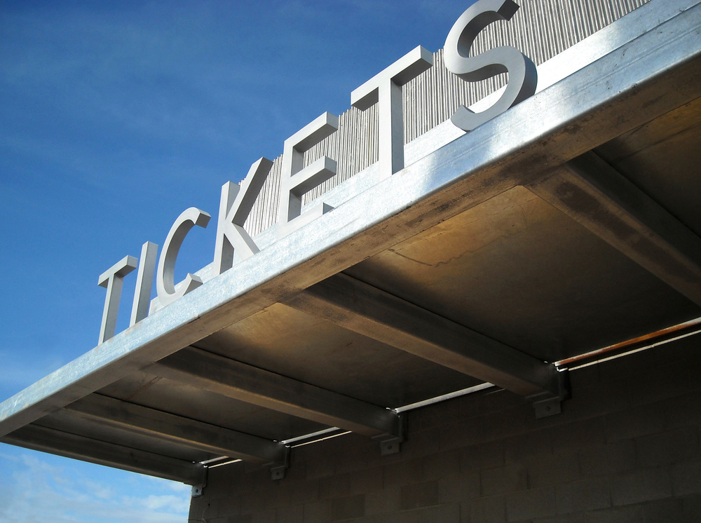 The ticket office is marked with vertically mounted aluminum encapsulated lettering.