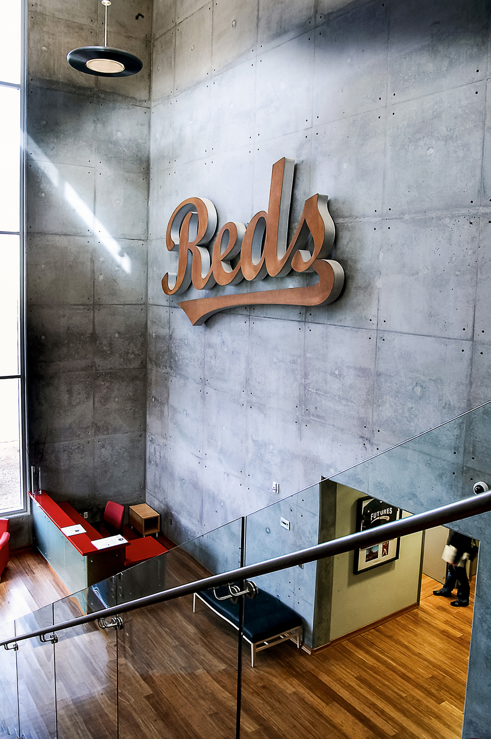 The Cincinnati Reds logo prominently brands the team as guests enter the lobby. The branding elements from both complexes are consistent in material and illumination.