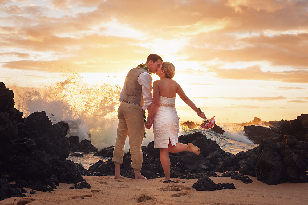 A Beach Wedding in Maui, Hawaii - the Bride and Groom pose as the waves crash with the sunset. Photo Credit: Jared Lawson Photography