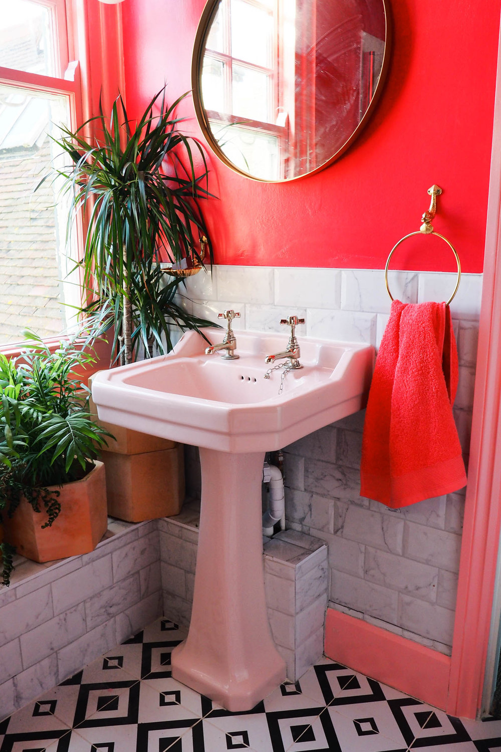 Amy's pink and marble bathroom with black and white tiles, green houseplants and brass accents.