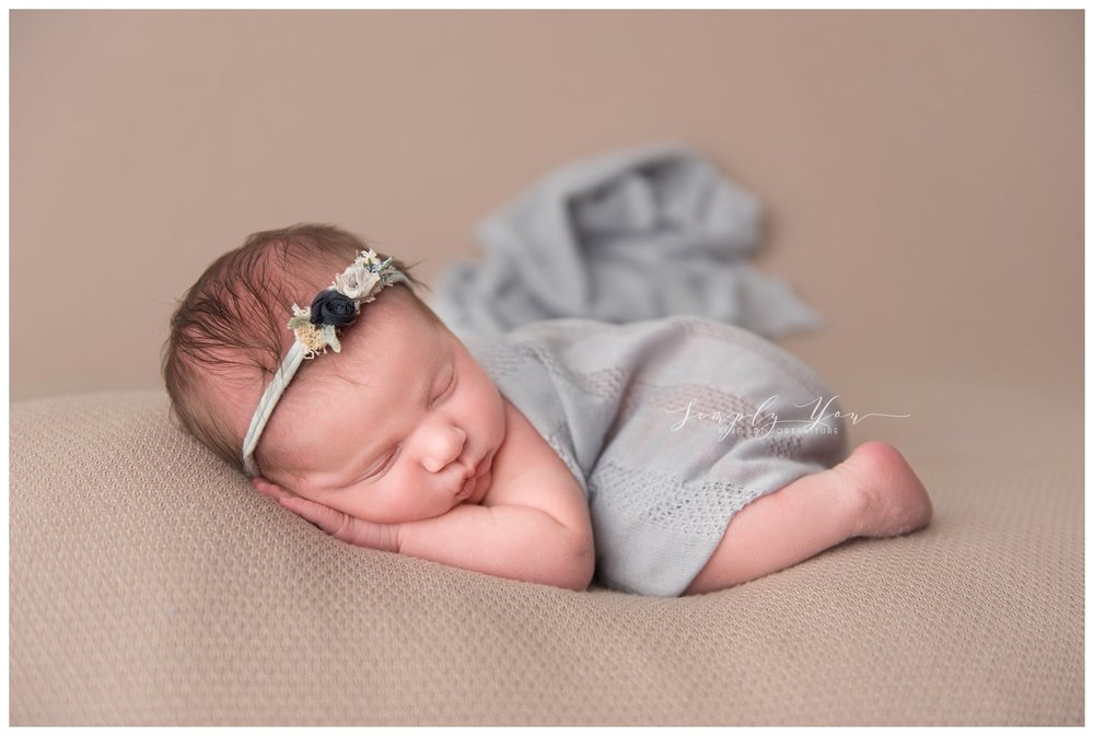newborn baby girl with blue wrap and organic headband