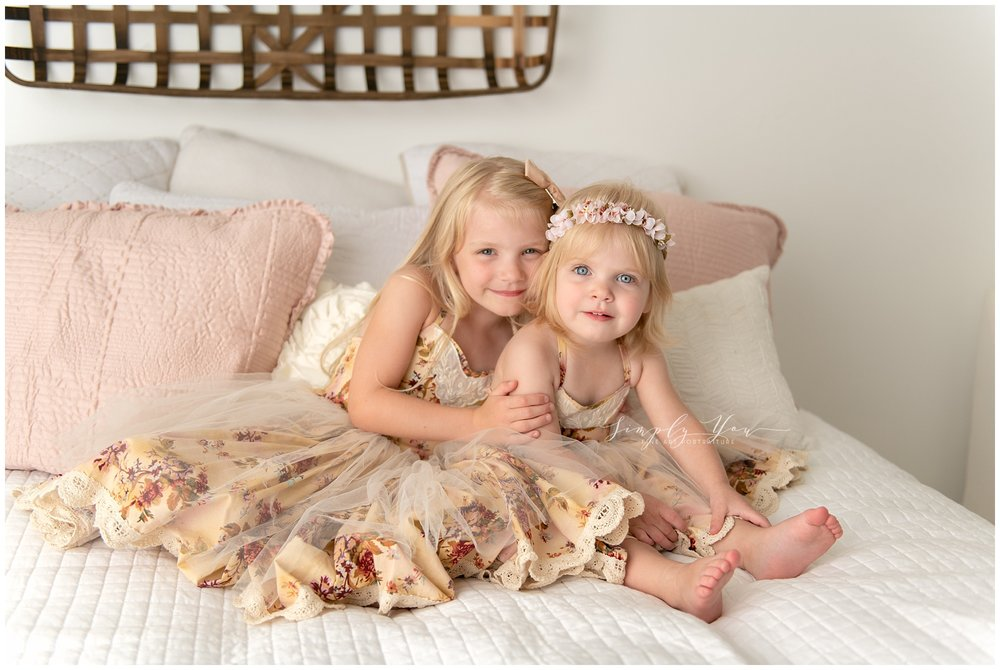 sisters in frilly dress white studio