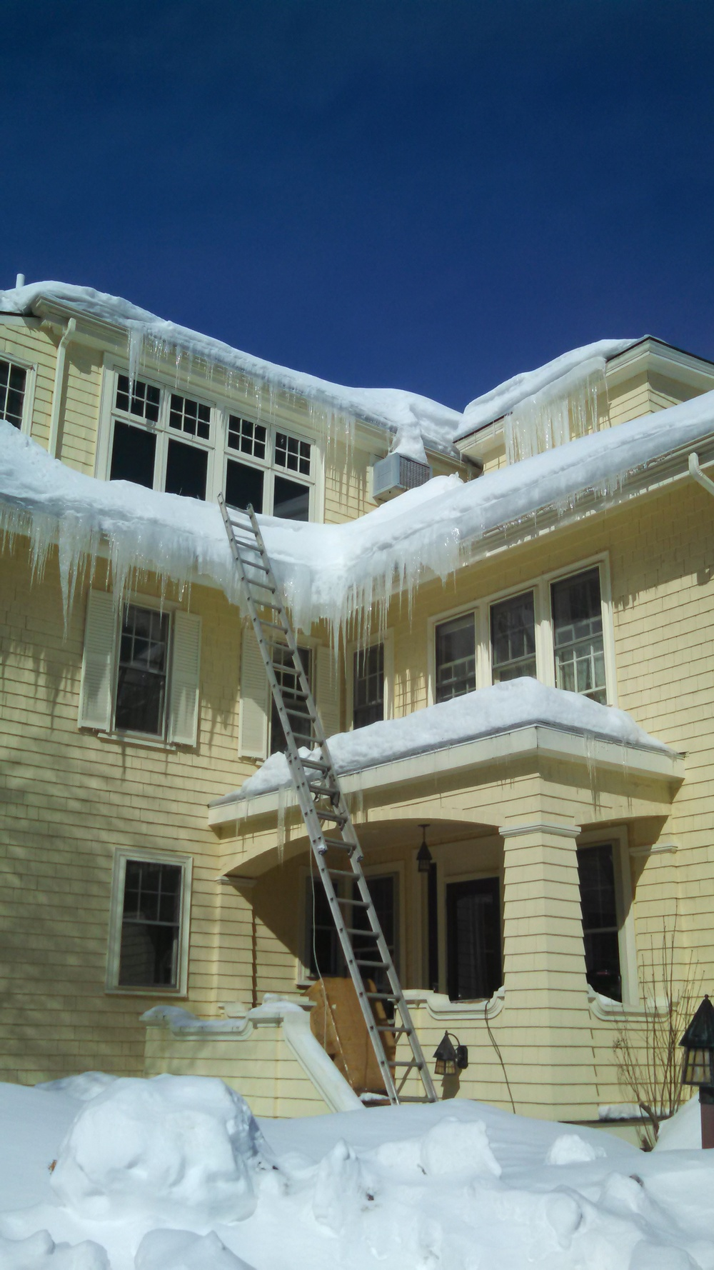 The larger the overhang of the roof, the more time you have to react. These icicles look problematic but actually they're not doing any major harm to the roof.