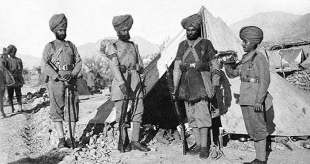 36th Sikhs, various ranks, 1896. On the left, holding his sword is an officer. He has a badge on his turban. Next is a Havildar with three stripes on his arm, then a Sepoy in winter dress and three good conduct stripes. On the right is a bugler. These last three other ranks do not wear a badge like the officer, but all four have a quoit circling their turbans. All four also wear boots instead of the sandals or shoes that so many of the infantrymen wore.