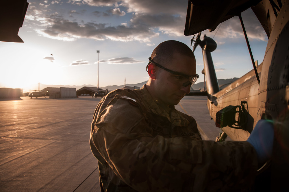 U.S. Army Specialist Anguish, Blackhawk mechanic, preflights and pulls a fuel sample, ensuring no decontamination is in our fuel system.