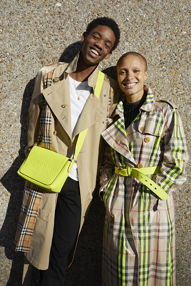 Montell Martin wearing a trench coat and neon soft leather crossbody bag and Adwoa Aboah wearing a laminated fluoro-trimmed check trench coat for Burberry captured by Juergen Teller.jpg
