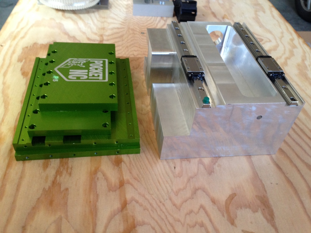 The base of our machine(left) was previously a box composed of 4 half inch walls.  To add rigidity to the machine and simplify assembly, we have moved to machining a solid billet of aluminum(right).