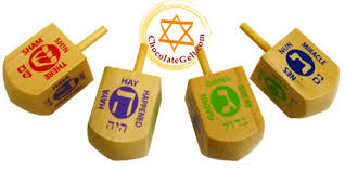 dreidels showing Hebrew letters Shin, Heh, Gimel, and Nun respectively