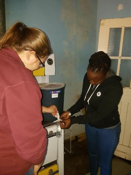 Meredith and Nkosi collecting water samples from a silver nitrate impregnated ceramic water filter at one of the participating households in Dertig