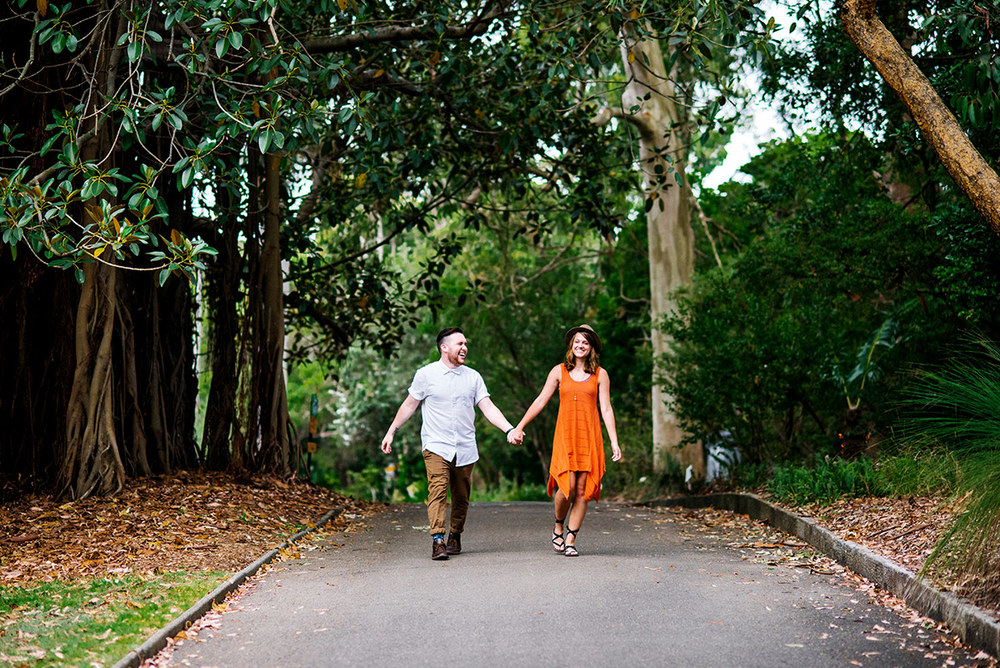 An engaged couple walks through the Botanic Gardens, Sydney