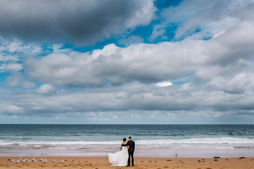 Weddings northern beaches - newlywed couple embrace on beach