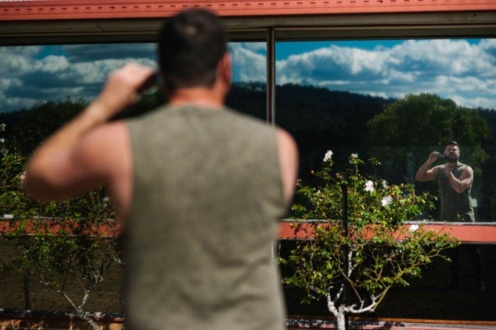 Groom shaving outside using window as a mirror