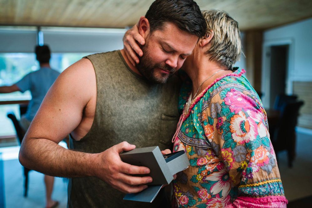 Groom and mother hug as groom opens gift from bride