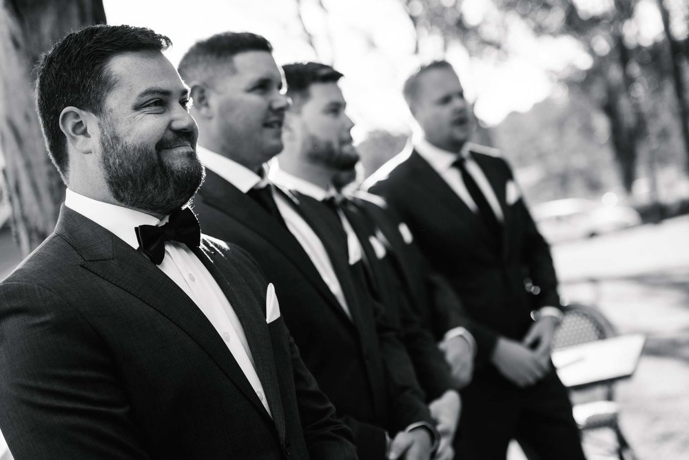 Groom watches bride walk down aisle