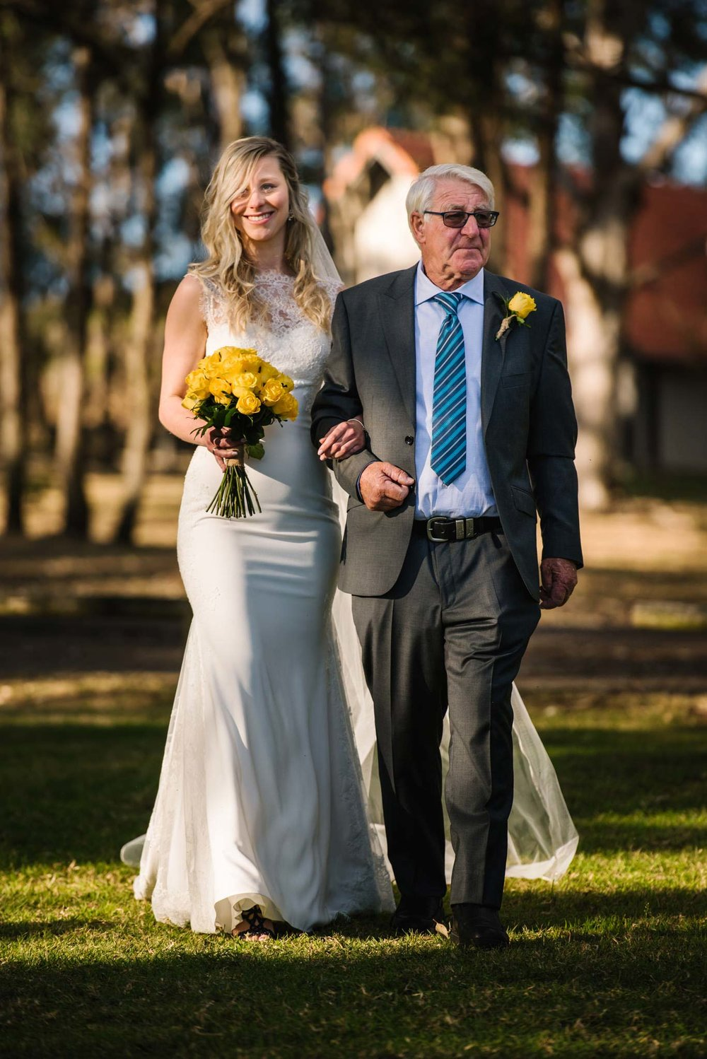 Bride and father walk down aisle during ceremony at Wandin Valley Estate