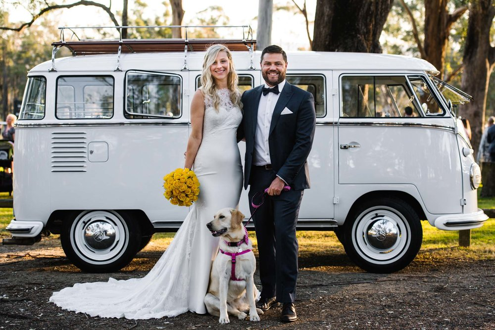 Bride, groom and yellow lab in front of white combi van