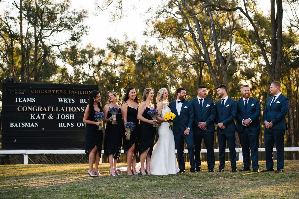 Bridal party in field at Wandin Valley Estate wedding with cricket score board in background