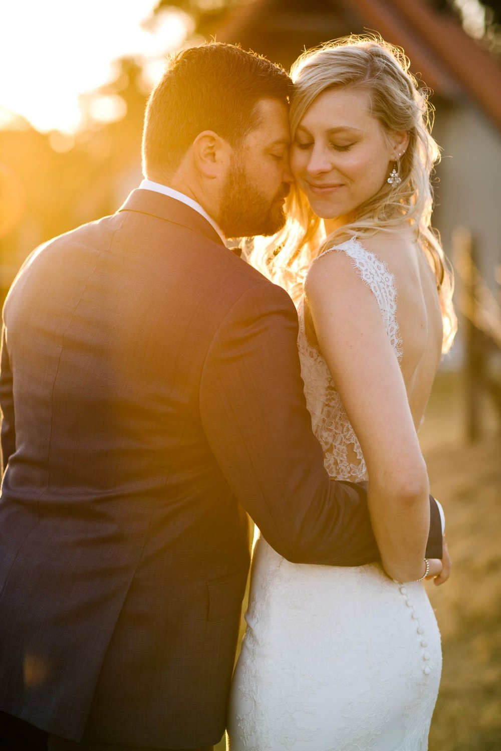 Backlit portrait of bride and groom with eyes closed