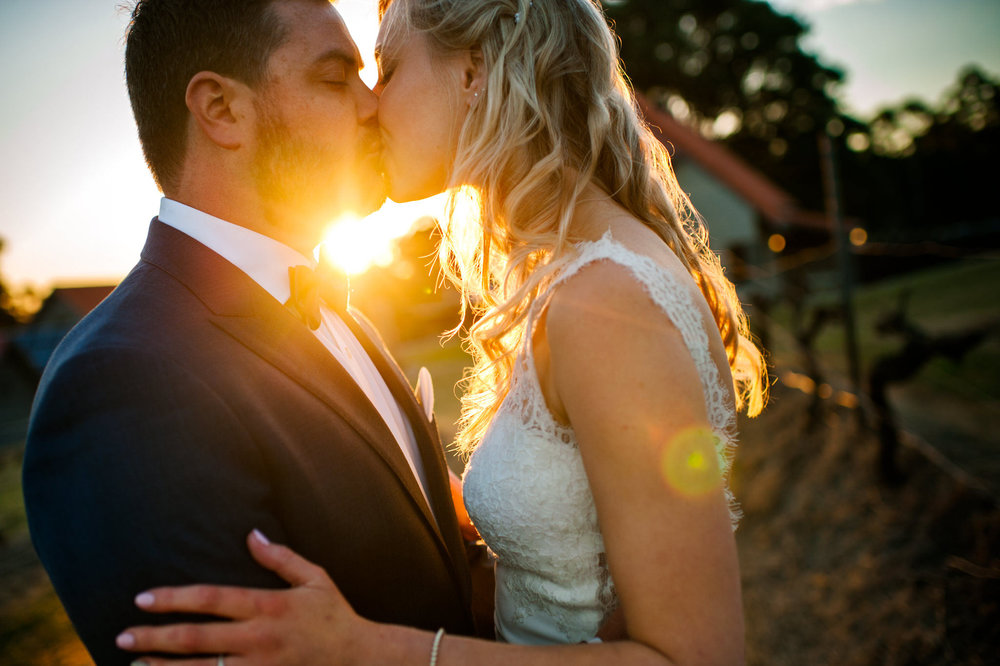 Bride and groom kissing with sun setting in the background