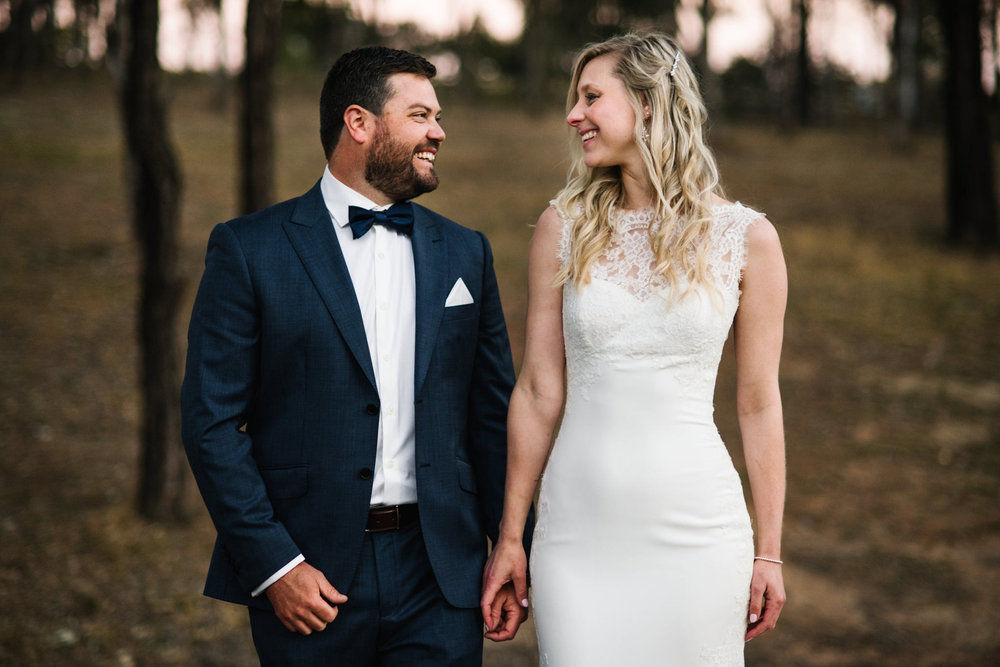 Happy newlyweds looking at each other with trees behind