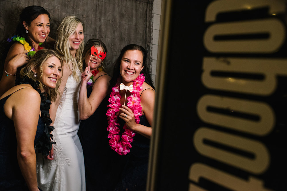 Bride and bridesmaid having fun in front of photo booth