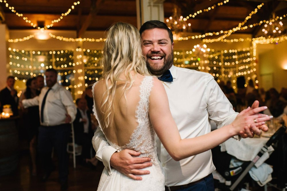Groom smiling during first dance with bride