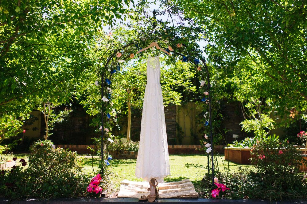 Grace Loves Lace bridal gown hanging in flowering garden