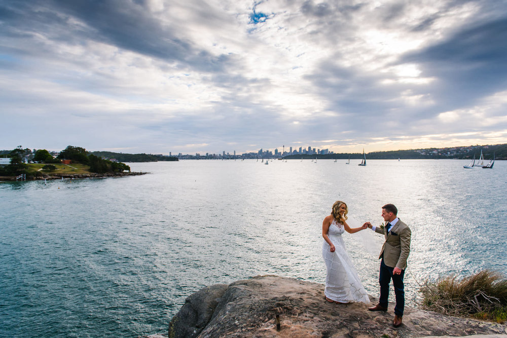 Bride and groom dance on headland at Camp Cove