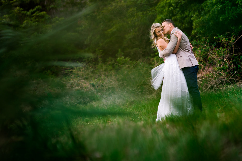 Bride smiles as groom hugs her in green forest backdrop