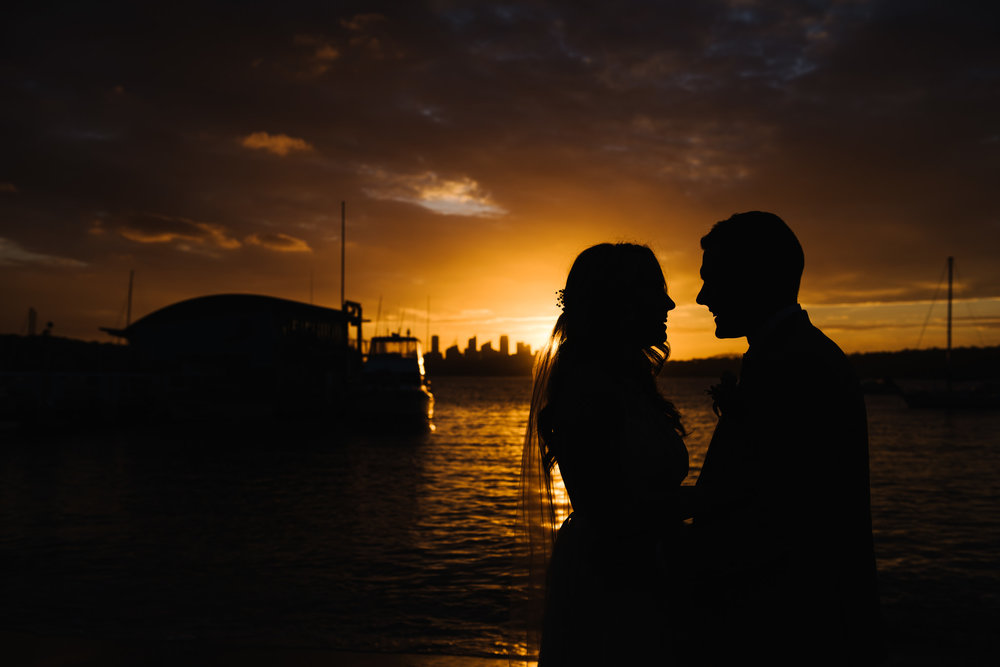 Bride and groom in front of amazing sunset at Watsons Bay Wharf