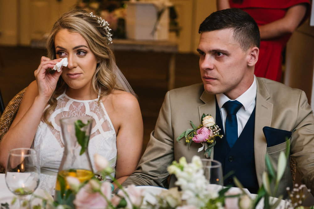Bride wiping tears away during father's speech