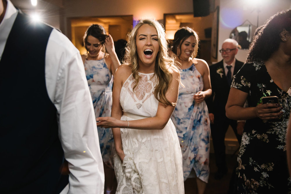 Bride laughing during line dance at wedding reception