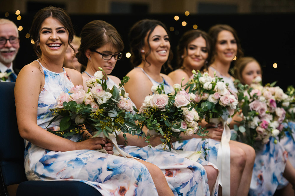 Happy bridesmaids in floral gowns during wedding ceremony