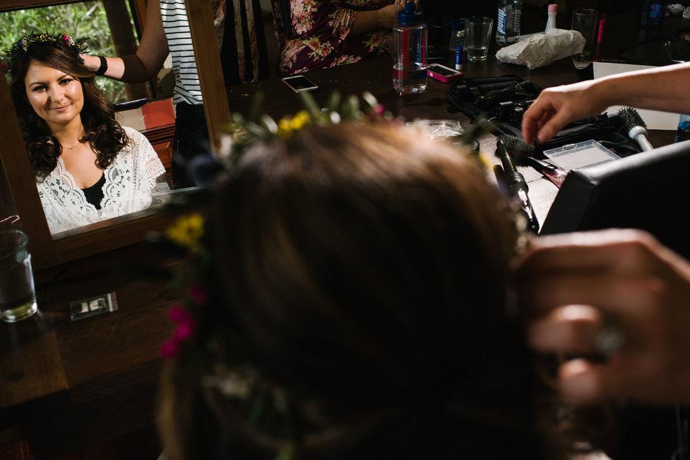 Bride looking in mirror during makeup application