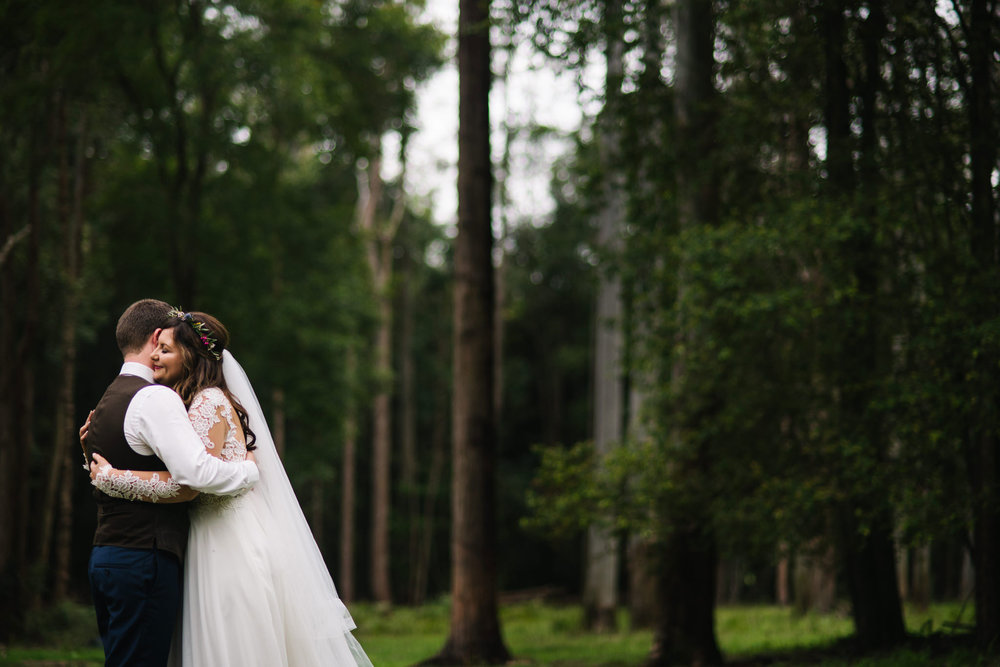 Bride and groom embrace in the woods