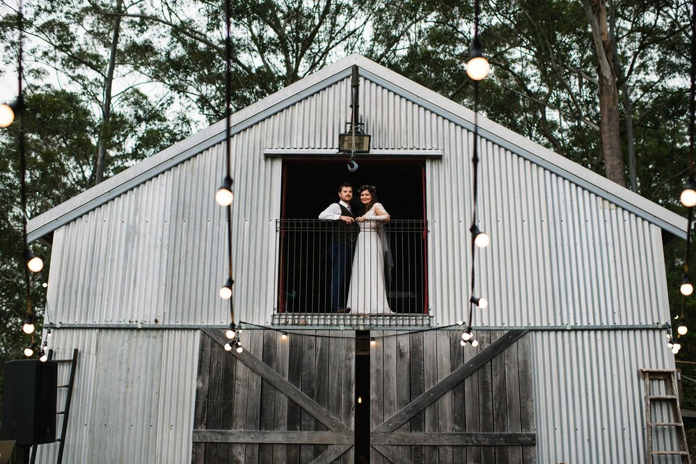 Bride and groom in window of steel barn