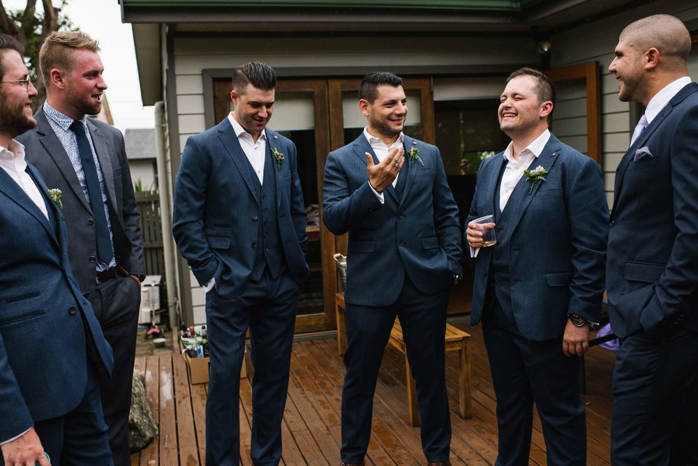 Groomsmen and groom laughing before ceremony