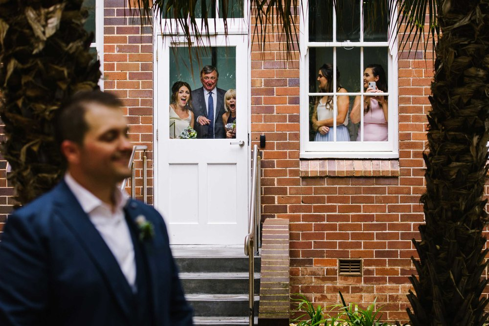 Family looking out window at groom before first look