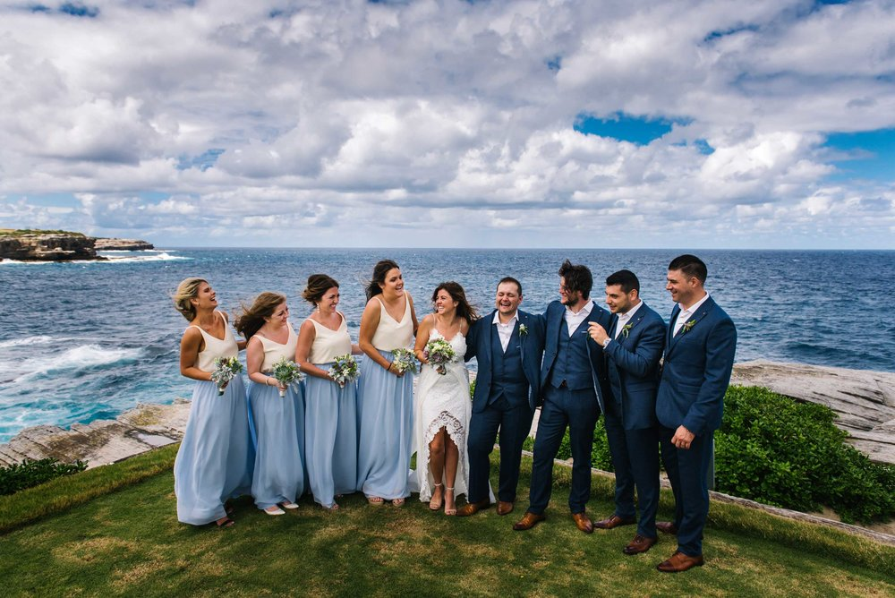 Bridal party laughing with Sydney coastline in the background
