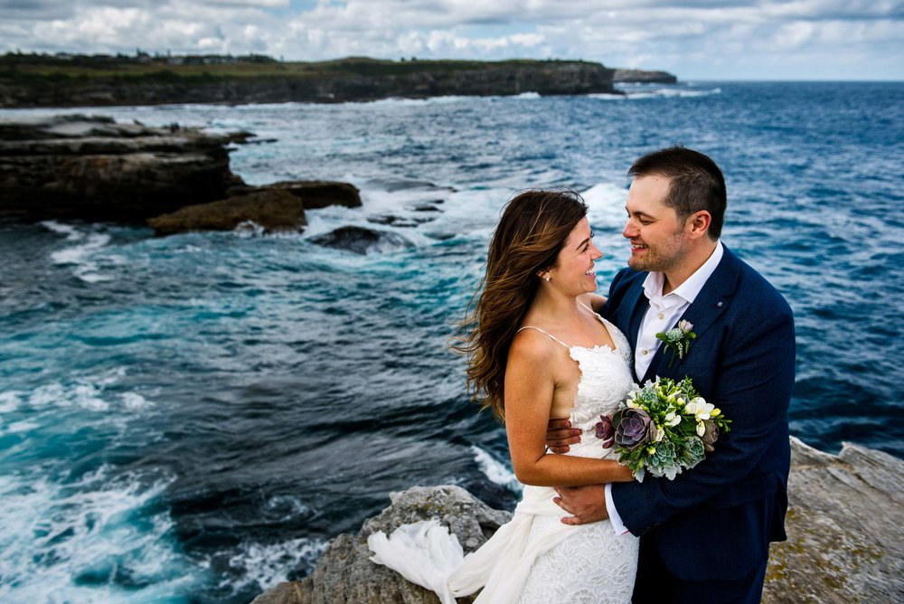 Bride and groom smile at eachother with views of Little Bay and the ocean in the background