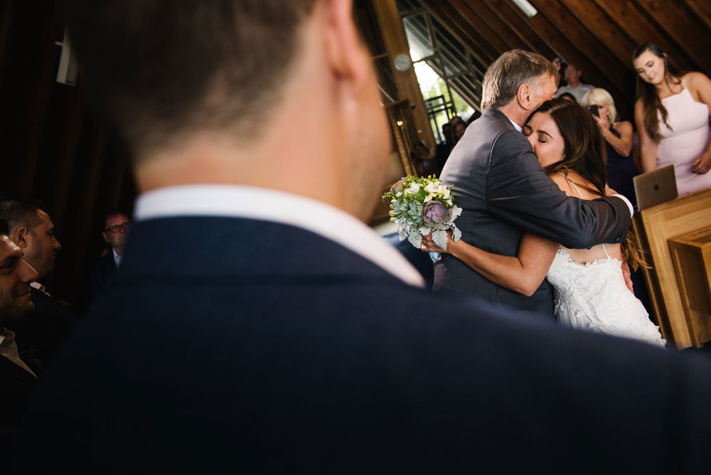 Bride hugs father as he gives her away to the groom