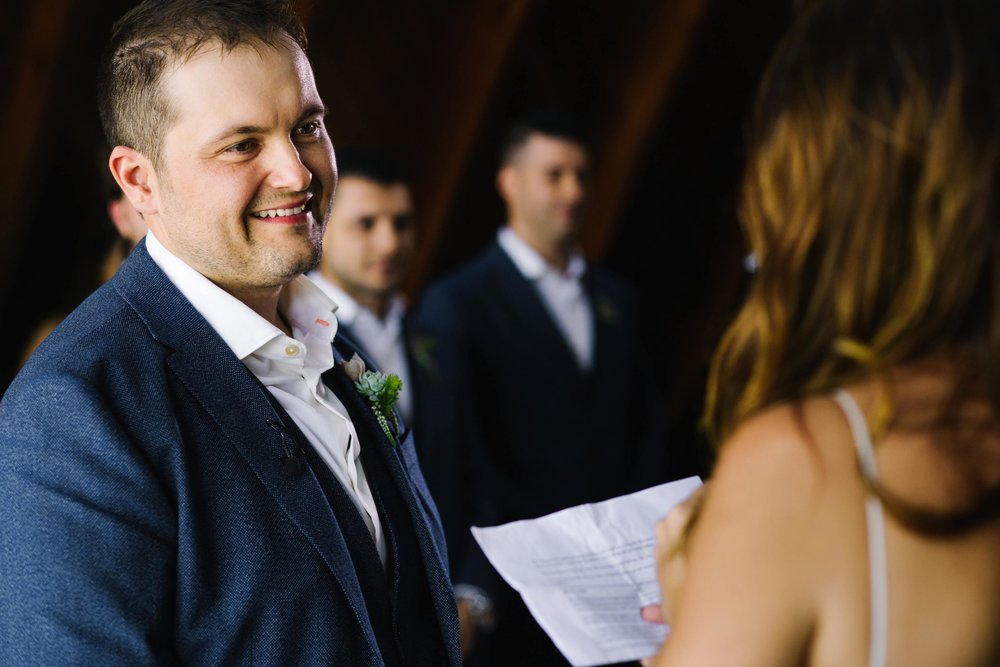 Groom smiles at bride during wedding ceremony
